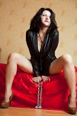 picture of sado-masochism  - beautiful young woman sitting on a couch and holding a chain - JPG