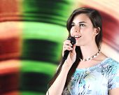 Постер, плакат: A beautiful teen soloist happily singing into her microphone with plenty of space for your text on h