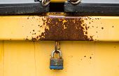 foto of dumpster  - a rusty yellow dumpster locked with a padlock - JPG