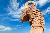 stock photo of viking ship  - Carved wooden dragon on forepart of the ancient Viking ship above dramatic blue sky - JPG
