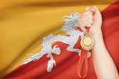Medal In Hand With Flag On Background - Kingdom Of Bhutan