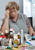 pic of health-care  - senior woman with a  row of many medicine bottles - JPG