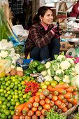 Unidentified Khmer woman selling greengrocery at traditional marketplace