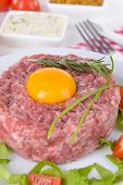 Delicious steak tartare with yolk on plate on table close-up
