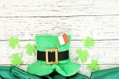 image of irish flag  - Saint Patrick day hat with clover leaves and Irish flag on wooden background - JPG