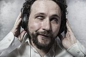 listening and enjoying music with headphones, man in white shirt with funny expressions