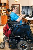 pic of wheelchair  - Man with spastic infantile cerebral palsy caused by a complicated birth sitting in a multifunctional wheelchair using a computer with a touch screen and wireless headset side view - JPG