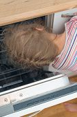 image of dangerous situation  - Little girl putting head into dishwasher - JPG