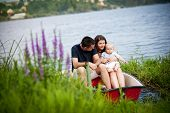 stock photo of life-boat  - Mother and father with baby boy on boat on lake - JPG