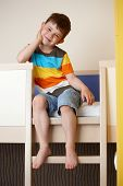 pic of bunk-bed  - Happy little kid sitting on bunk bed - JPG