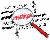 stock photo of interrogation  - Magnfiying glass on the word investigate to illustrate detective or police work researching facts in a case - JPG
