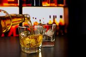 stock photo of whiskey  - barman pouring whiskey in front of whiskey glass and bottles on wood table - JPG