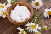 foto of chamomile  - Beauty cream in bowl with chamomile on wooden background - JPG