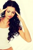 stock photo of hangover  - Young woman holding her head in pain suffering from a headache - JPG