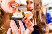 stock photo of chocolate muffin  - Friends having fun and eating muffins at bakery or pastry shop  - JPG