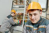 pic of fuse-box  - two electrician builder engineer workers in front of fuse switch box - JPG