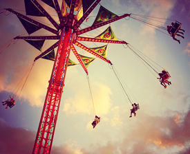 foto of carnival ride  - a fair ride shot with a long exposure at dusk toned with a retro vintage instagram filter  - JPG