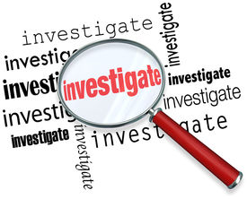 stock photo of investigation  - Magnfiying glass on the word investigate to illustrate detective or police work researching facts in a case - JPG