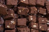 image of chocolate fudge  - Almond fudge is sliced and stacked on a plate ready to be served - JPG