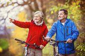 foto of bike path  - Active seniors having walk with bike in autumn nature - JPG