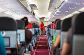 stock photo of air hostess  - Interior of airplane with passengers on seats and stewardess in red uniform at the aisle - JPG