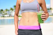 stock photo of smoothies  - Fitness woman drinking green vegetable smoothie after running exercise - JPG