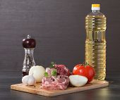 image of lamb chops  - raw lamb leg chops on a wooden chopping board with garlic onion pepper tomato and vegetable oil  - JPG
