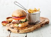 image of wooden basket  - Burger with meat and French fries in basket on wooden background - JPG