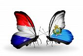 stock photo of holland flag  - Two butterflies with flags on wings as symbol of relations Holland and San Marino - JPG