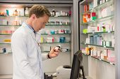 image of hospital  - Handsome pharmacist using the computer at the hospital pharmacy - JPG