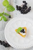stock photo of mountain-ash  - canape with cottage cheese and black berries of mountain ash in a plate and fresh mint leaves on a white wooden background - JPG
