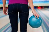stock photo of bowling ball  - Rear view of young women holding a bowling ball while standing against bowling alleys - JPG