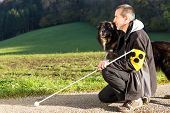 stock photo of attention  - A blind man kneels next to his attentive guide dog - JPG