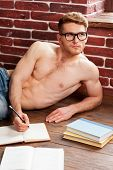 foto of shirtless  - Thoughtful young shirtless man writing something in note pad and looking away while lying on the floor at his apartment - JPG