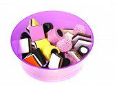 stock photo of laxatives  - Many colorful liquorice allsorts sugar candies in a pink bowl over white - JPG