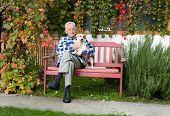 picture of lap  - Senior man hugging his dog on his lap on bench - JPG