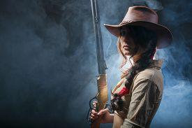 pic of girls guns  - girl cowboy with a gun on a gray background - JPG