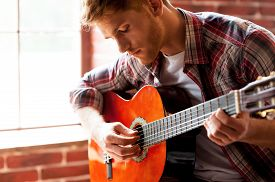 foto of string instrument  - Close-up of young man playing acoustic guitar while sitting in front of the window ** Note: Visible grain at 100%, best at smaller sizes - JPG