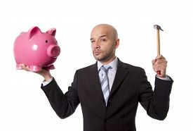 picture of spanish money  - bald Hispanic businessman with hammer in his hand holding pink piggybank ready to break the piggy bank and take money and savings out isolated on white background - JPG