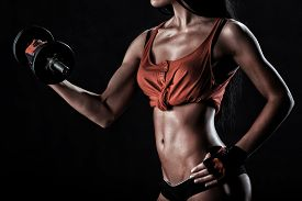 stock photo of elbow  - beautiful woman on a dark background is engaged in fitness - JPG