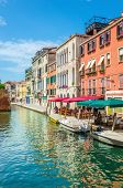 foto of gondolier  - Scenic canal with italian restaurant and colorful buldings, Venice, Italy