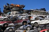 foto of junk-yard  - Low Angle View of Old Squashed Cars Stacked at Junk Yard with Blue Sky in Background - JPG