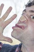 stock photo of lunate  - Crazy lunatic man smooshes face against glass surfaces - JPG
