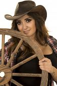 foto of cowgirls  - a cowgirl with a smile holding on to a wagon wheel - JPG