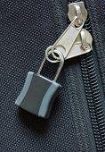stock photo of zipper  - zipper locked on black canvas bag background - JPG