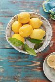 picture of ceramic bowl  - Fresh lemons with leaves in in rustic ceramic bowl over wooden background - JPG
