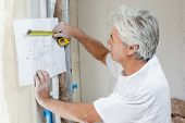 picture of measurements  - Builder measuring blueprints with tape measure - JPG