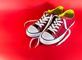 picture of backround  - Red and white canvas style sneakers on a red backround - JPG
