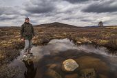 stock photo of boggy  - Man traveler on marshland against the backdrop of rain clouds - JPG