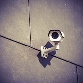 foto of cctv  - White security camera on gray office building safety surveillance system outside looking around in city urban scene cctv electronics industry concept - JPG